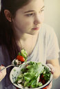 Teenager girl with cut cucumber tomato salad bowl Royalty Free Stock Photo