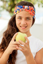 Teenager girl eating a apple with blue eyes Royalty Free Stock Images