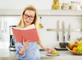 Teenager girl having sandwich in kitchen while studying glasses Royalty Free Stock Photos