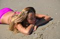 Teenager girl laying in sand wearing pink bikini a tan teenage with her head on her crossed arms while the her Stock Photo