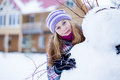 Teenager girl making snowman outdoors in front of house Royalty Free Stock Images