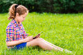 Teenager girl sitting on the grass with digital tablet on her knees beautiful in casual clothes reading and surfing outdoor Royalty Free Stock Photography