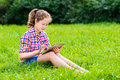 Teenager girl sitting on grass with digital tablet outdoor portrait of a pretty in casual clothes the her knees reading and Royalty Free Stock Image