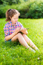 Teenager girl sitting on grass with digital tablet outdoor portrait of a pretty in casual clothes the her knees reading and Stock Photography