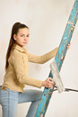 The teenager girl  on a step-ladder Royalty Free Stock Image