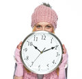 Teenager girl in winter hat and scarf hiding behind clock high resolution photo Royalty Free Stock Photography