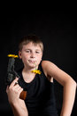 Teenager with a gun and flowers on black background Stock Images