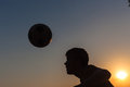 Teenager heads football silouette s the or soccer ball silhouetted at sunset Royalty Free Stock Images