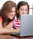 Teenager and her mother browsing the web working on a laptop computer or isolated on white Stock Photography