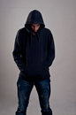 Teenager with hoodie looking down against a gray wall Stock Photos
