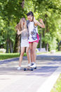 Teenager Lifestyle Ideas and Concepts. Two Teenage Girlfriends Having Fun Skating Longboard in Park Outdoors