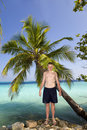 Teenager at palm tree Royalty Free Stock Image