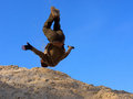 Teenager performs freerunning somersault on sand hill shot in the dnieper sands ukraine Stock Image