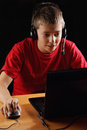 Teenager playing on laptop in darkness Stock Image
