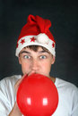 Teenager with red balloon in santa s hat inflate on the dark background Stock Image