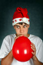 Teenager with red balloon in santa s hat inflate on the dark background Royalty Free Stock Images