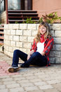 Teenager in red skirt sitting on sidewalk Royalty Free Stock Photos