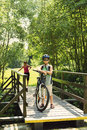 Teenager relaxing on a bike trip on wooden bridge in sunny day Stock Photos