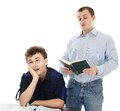 Teenager sitting at his desk showing boredom while his father is studio shot of a reading loudly isolated over white background Stock Photos