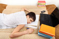 Teenager sleeps after learning on the sofa at the home Stock Photos