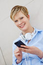 Teenager with smartphone and headphones happy outdoors in city Royalty Free Stock Photography