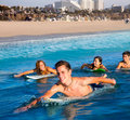 Teenager surfer boys and girls swimming ove surfboard group over the in santa monica california Royalty Free Stock Image