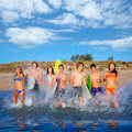 Teenager surfers group running beach splashing surfer teenagers boys and girls happy to the water Royalty Free Stock Images