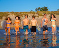 Teenager surfers group running beach splashing surfer teenagers boys and girls happy to the water Stock Photos