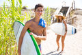 Teenager surfers waling to the beach walking in sunny summer day Stock Image