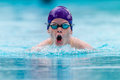 Teenager swim gala goggles boy racing in in breast stroke style straight on action Stock Images