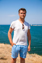 Teenager in t shirt posing near sea handsome Stock Photography