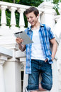 Teenager with tablet while standing near the stairs Royalty Free Stock Photo