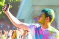 Teenager taking photo on mobile phone on holi color festival Royalty Free Stock Photo
