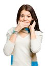 Teenager talking on phone and covering her mouth with hand isolated white Royalty Free Stock Images