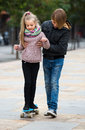Teenager teaching sister skateboarding smiling teenage boy younger in fall day Royalty Free Stock Images