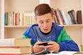 Teenager texting with smartphone while studying playing or Stock Photography