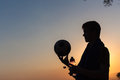 Teenager water bottle football silouette s holds a and ball after playing game silhouetted at sunset Royalty Free Stock Images