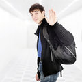 Teenager wave goodbye with knapsack in the white corridor Royalty Free Stock Image