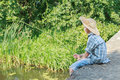 Teenager with wooden rustic fishing rod angling on concrete bridge Royalty Free Stock Photo