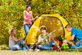 Teenagers build yellow tent themselves in forest Royalty Free Stock Photo