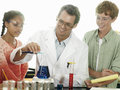 Teenagers doing science experiment at desk in classroom teacher assisting smiling Royalty Free Stock Images