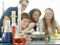 Teenagers doing science experiment teacher assisting focus on conical flasks in foreground Royalty Free Stock Photos