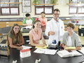 Teenagers doing science experiments at desks in classroom teacher assisting portrait Stock Image