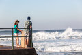 Teenagers girl boy tidal pool ocean waves at beach standing talking watching Royalty Free Stock Photos