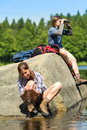 Teenagers resting and birdwatching by lake young hikers sporty Stock Photography
