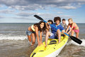 Teenagers in sea with canoe Stock Image