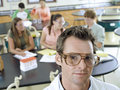 Teenagers sitting at desks in classroom focus on science teacher in foreground portrait Stock Image