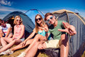 Teenagers sitting on the ground in front of tents Royalty Free Stock Photo