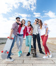 Teenagers with skates outside summer holidays and teenage concept group of Royalty Free Stock Image
