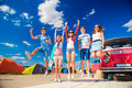 Teenagers at summer festival jumping by vintage red campervan